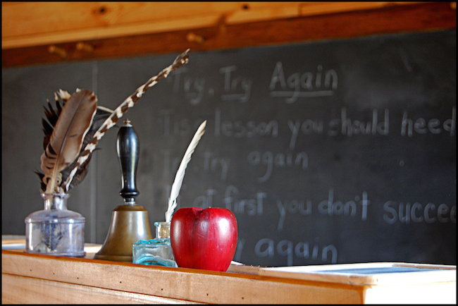 quill pen and apple on podium in front of chalkboard